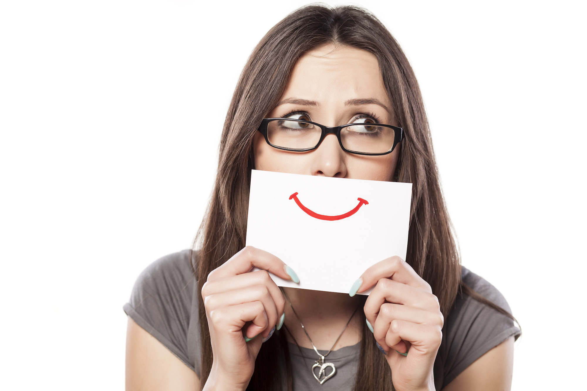 This is an image of a woman putting a smiley face sign over her mouth. Adoptees can break away and be free from faking smiles and happiness.