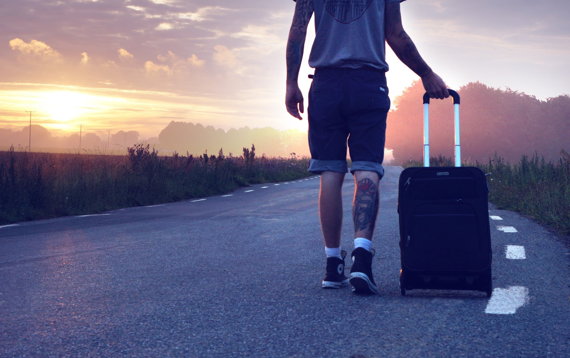 Photo of young man pulling suitcase and walking down country road is symbolic of adoptees and foster kids' desire to search for lost birth relatives. The traveler here is pulling a suitcase full of something that will keep him crippled with fear. Sherrie shows how to let go of the suitcase and run forward.